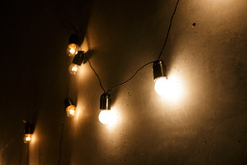 a garland of electric bulbs hanging on the wall