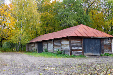Wooden barn with red roof. Autumn trees in the background