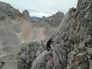 Man on via ferrata at on the way up to Škrlatica 2,740 m with trail marks on the rocks.