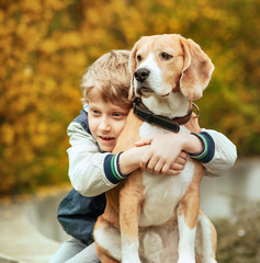 Two best freinds portrait - little boy hugs beagle dog
