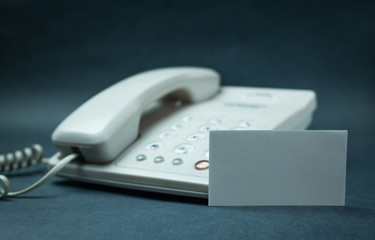 Office phone with blank business card on a blue background.