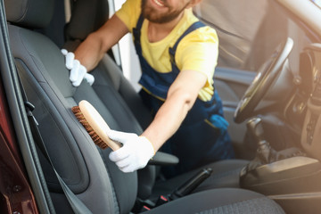 Man cleaning salon with brush in car