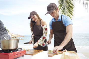 Young couple wearing aprons preparing food on beach
