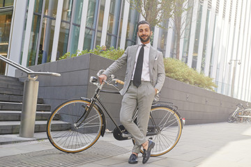 Portrait of young man in suit with bicycle