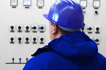 Technician with blue  helmet control instruments in power plant