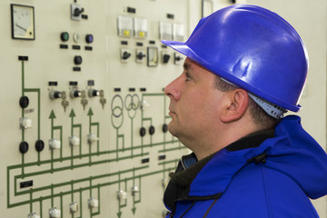 Engineer with red  helmet control instruments in power plant