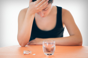 Woman woman with headache taking medication, or pills with a glass of water. Depressed woman concept taking antidepressant pills.