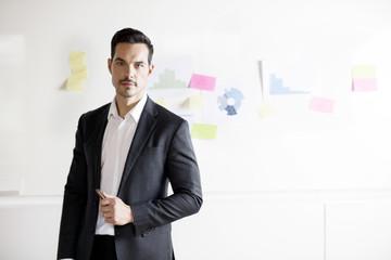Portrait of businessman in office by graphs on bulletin board
