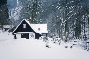 Challet in snowy mountains country, foggy winter day, Czech republic