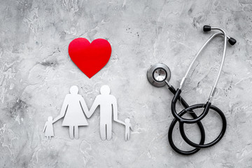Take out health insurance for family. Stethoscope, paper heart and silhouette of family on grey stone background top view