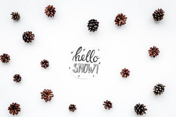 Hello snow hand lettering. Winter pattern with pinecones on white background top view
