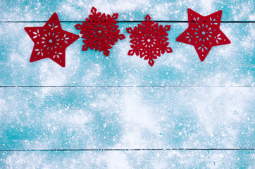 Red snowflakes border teal blue background with snow texture; holiday sign with white copy space