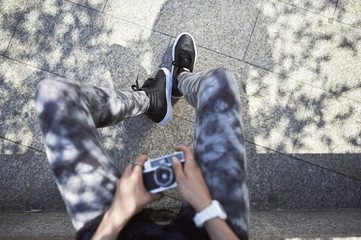 Teenage girl holding camera while sitting