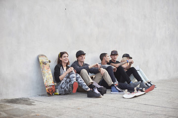 Teenage friends sitting by skateboard