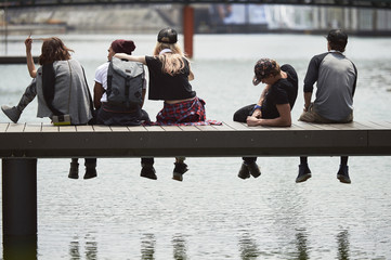 Teenage friends sitting on jetty over river