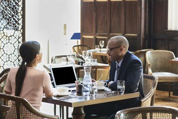Businesspeople using laptop during meeting at cafe
