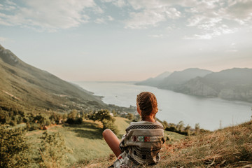Girl sitting on a hill at Lake Garda in Italy