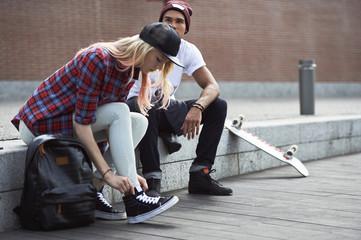 Teenage girl tying shoelace by boardwalk