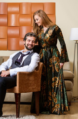 Picture of elegant businessman on chair and long-haired blonde in dress