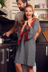 Picture of happy loving couple preparing food in kitchen