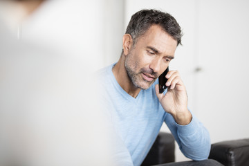 Mature businessman talking on smartphone in office