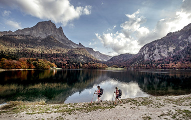 Young women hiking by lake and mountain