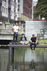 Teenage boys on jetty with skateboard