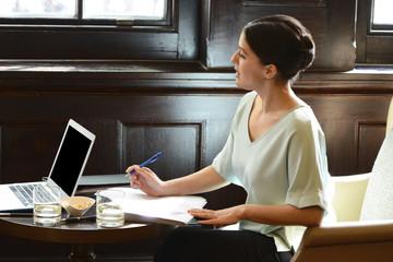 Businesswoman working at bar