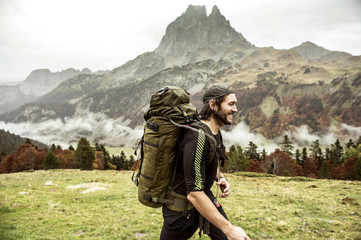 Smiling young man hiking by mountain