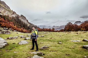Portrait of smiling man hiking in field beneath mountain