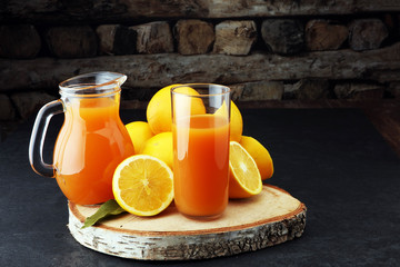 glass jar of fresh orange juice with fresh fruits on dark table