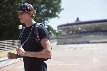 Teenage boy holding earphones in courtyard
