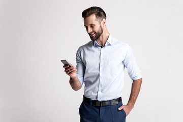 Great email! Handsome young man using his phone with smile while standing against white background. Fototapete