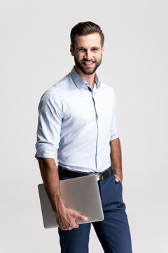 Successful at his work. Handsome young man holding his laptop and looking at camera with smile while standing against white background.