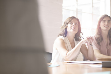 Mature businesswoman listening during meeting in conference room