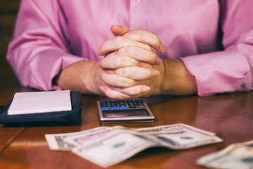Hands folded over a table, female accountant counting money with calculator. Dollar bills on a wooden desk.