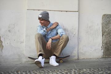 Teenage boy sitting on skateboard