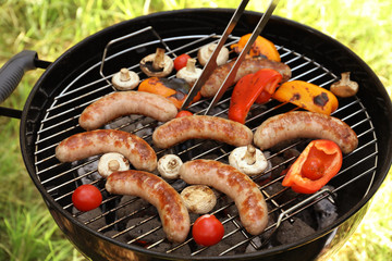 Sausages and vegetables on barbecue grill outdoors