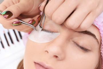 Young woman undergoing eyelash extensions, closeup