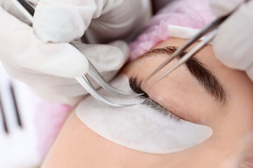 Young woman undergoing eyelash extensions, closeup