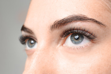 Young woman with eyelash extensions on grey background, closeup