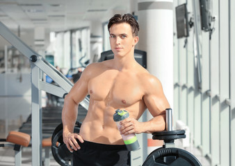 Sporty young man with protein shake in gym