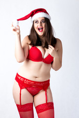 Happy cute fat Santa girl. Model in red lingerie and Santa hat. XXL woman celebrating Christmas and New Year