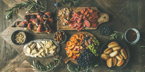 Flat-lay of holiday, party, family dinner table set with wine snacks. Meat, cheese, olives, sandwiches, prosciutto, buns, wooden background, top view. Fingerfood or catering food concept