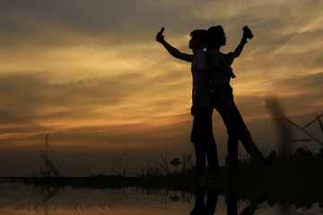 silhouette of a couple standing selfie on the riverside, have meadow on scary sky.