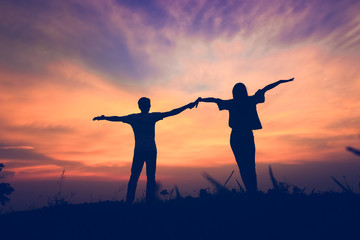 silhouette of a couple standing and stretch the arms on beauty sunset.