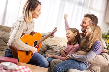 Happy loving family. Pretty young mother,daughter and husband playing guitar together