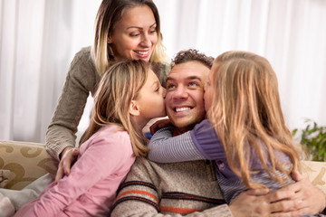 beautiful young parents and their cute little daughters, hugging smiling, Girl is kissing her dad