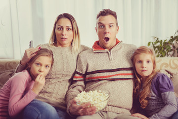 Beautiful young parents and their children are watching TV, eating popcorn and  sitting on couch at home