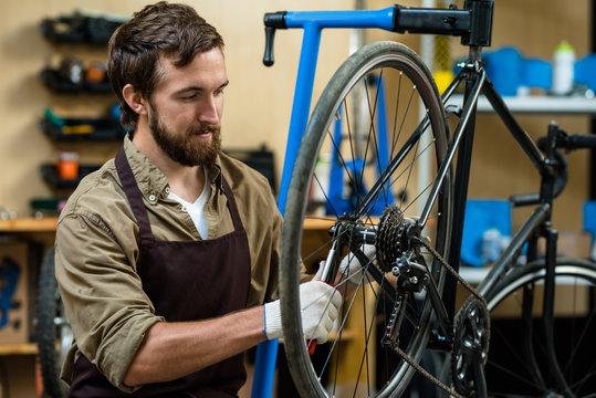 Master in apron fixing cogwheel of bike during working day